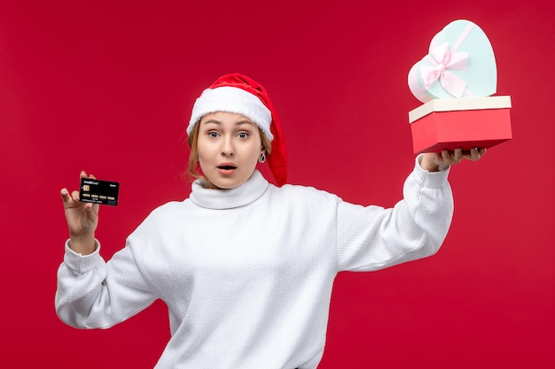 Front view young woman holding gifts and bank card on red desk