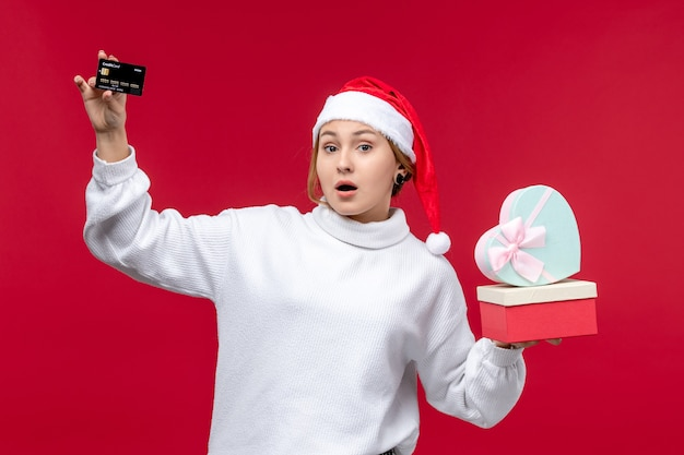 Front view young woman holding gifts and bank card on red floor holiday christmas red