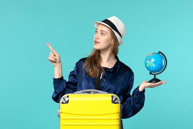 地球儀を保持し、青い背景の女性の休暇旅行航海水上飛行機で休暇の準備をしている正面図若い女性