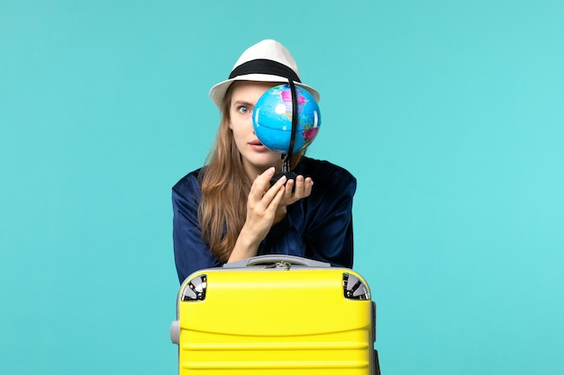 Front view young woman holding globe and preparing for vacation on blue background female journey voyage sea plane vacation