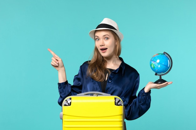 Front view young woman holding globe and preparing for vacation on a blue background female vacation journey voyage sea plane