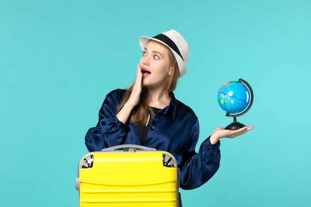Front view young woman holding globe and preparing for vacation on the blue background female vacation journey voyage sea plane