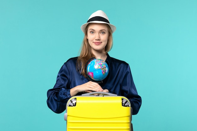 Front view young woman holding globe and preparing for vacation on blue background plane female vacation journey voyage sea