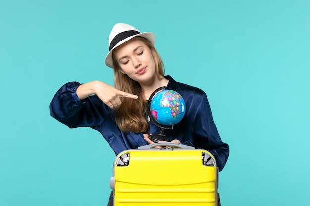 Front view young woman holding globe and preparing for vacation on the blue background plane female vacation journey voyage sea