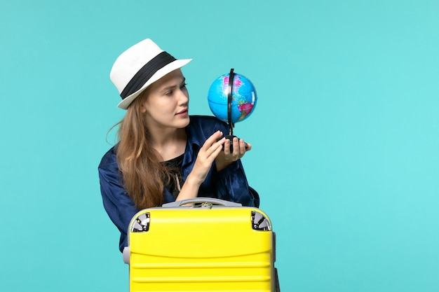 Front view young woman holding globe and preparing for vacation on blue desk female vacation journey voyage sea plane