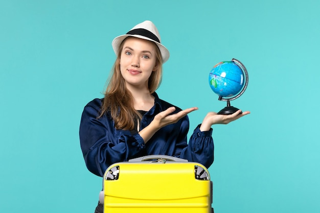 Front view young woman holding globe and preparing for vacation on blue desk plane female vacation journey voyage sea