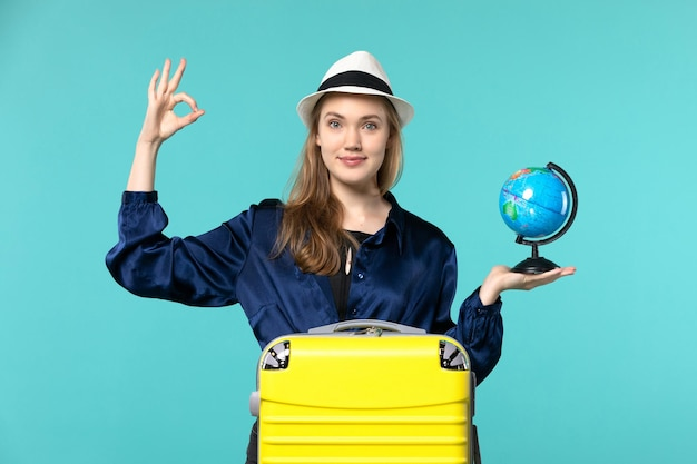 Front view young woman holding globe and preparing for vacation on blue floor plane female vacation journey voyage sea