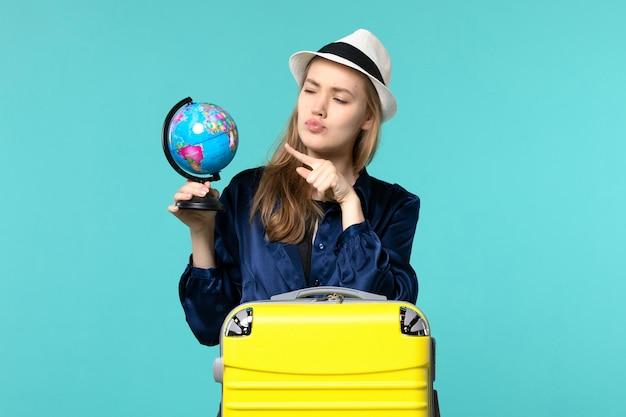 Vista frontale della giovane donna che tiene il globo e che si prepara per le vacanze su sfondo azzurro