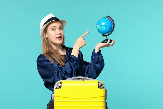 Front view young woman holding globe and preparing for vacation on light blue background plane female vacation journey voyage sea