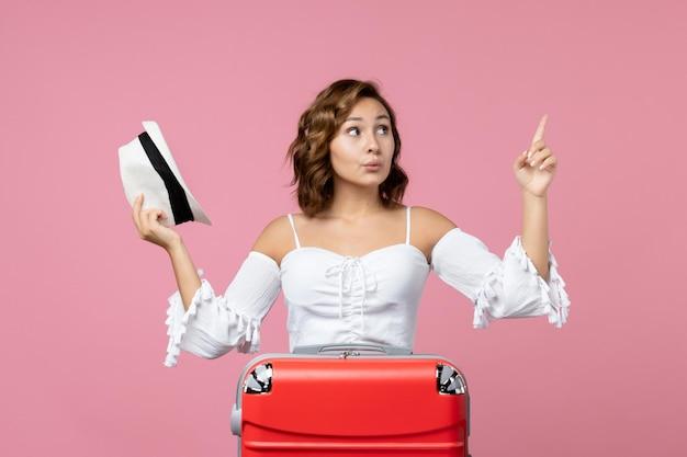 Vista frontale della giovane donna che tiene il cappello e si prepara per il viaggio con la borsa rossa sul pavimento rosa colore mare modello vacanza viaggio viaggio
