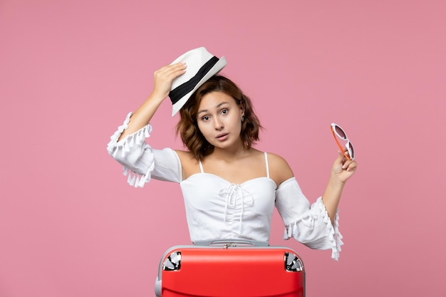 Vista frontale della giovane donna che tiene in mano cappello e occhiali da sole con borsa rossa su un viaggio di viaggio di vacanza modello di mare di colore rosa