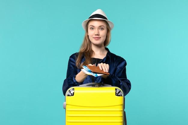 전면보기 젊은 여자가 그녀의 티켓을 들고 파란색 배경 여행 비행기 바다 휴가 여행 항해에 여행을 준비