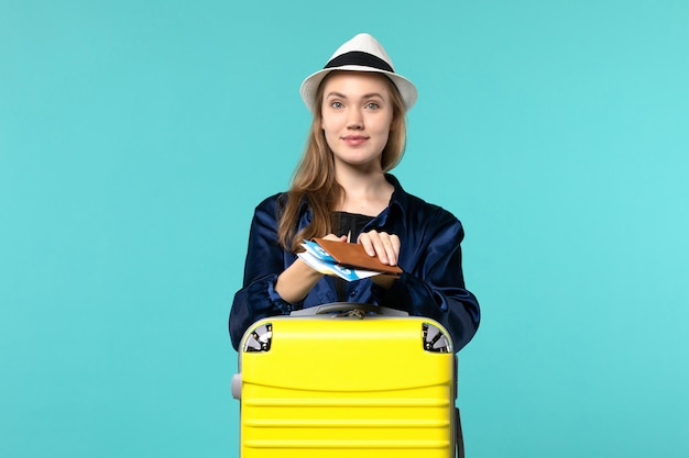 Front view young woman holding her tickets and preparing for trip on blue background journey plane sea vacation travel voyage