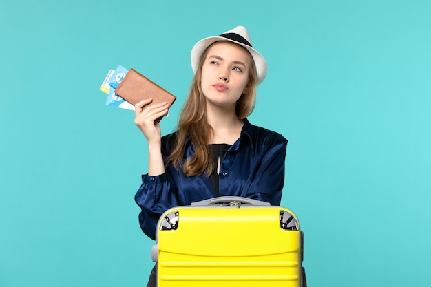 Front view young woman holding her tickets and preparing for trip on the blue background journey plane sea vacation travel voyage