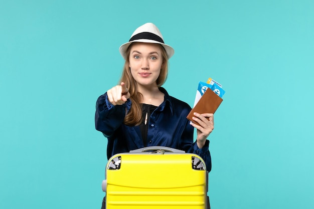 Front view young woman holding her tickets and preparing for trip on the blue background journey voyage plane sea vacation travel