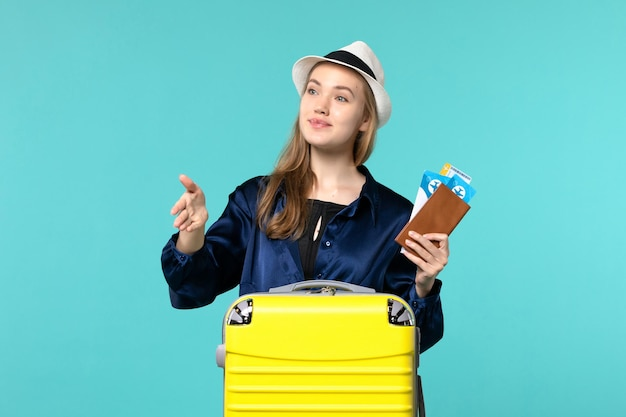 Front view young woman holding her tickets and preparing for trip greeting someone on blue background journey voyage plane sea vacation travel