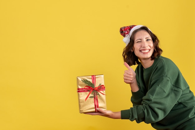 Front view of young woman holding little christmas present on yellow wall