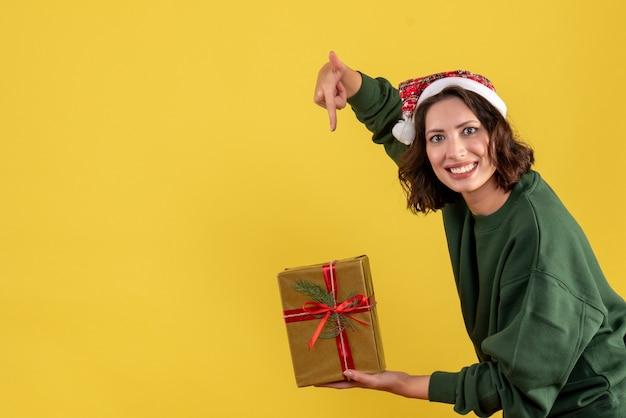 Vista frontale della giovane donna che tiene poco regalo di natale sulla parete gialla
