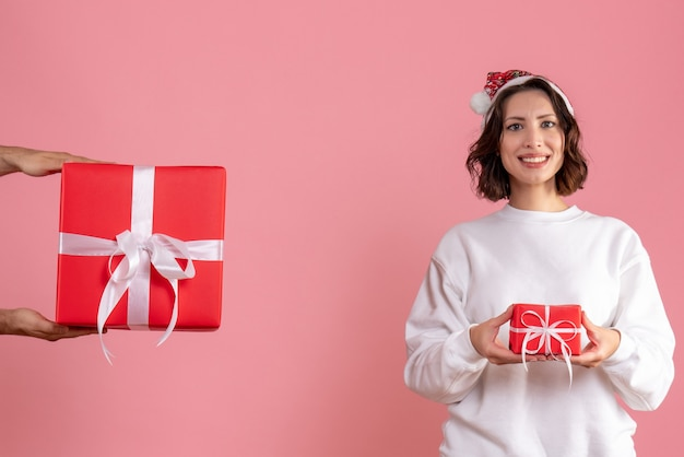 Front view of young woman holding little present and accepting gift from man on pink wall