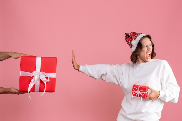 Front view of young woman holding little present and not accepting gift from man on pink wall