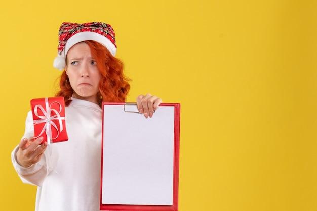 Vista frontale della giovane donna che tiene poco regalo di natale e nota di file con la faccia triste sulla parete gialla