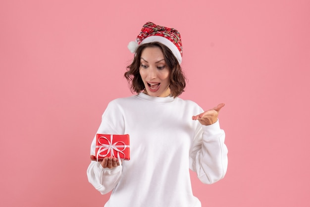 Front view of young woman holding little xmas present on pink wall
