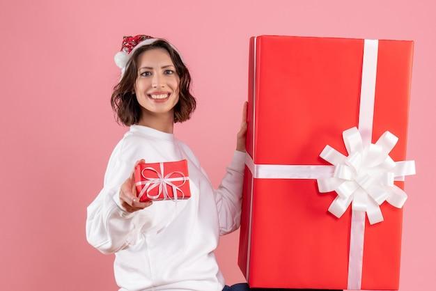 Vista frontale della giovane donna che tiene un piccolo regalo di natale con uno enorme sulla parete rosa