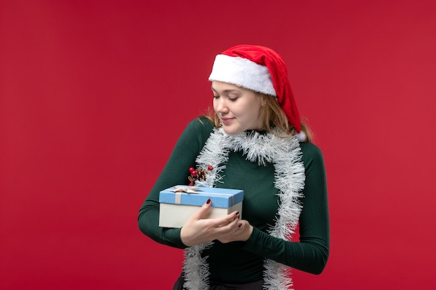 Front view young woman holding new year present on a red background