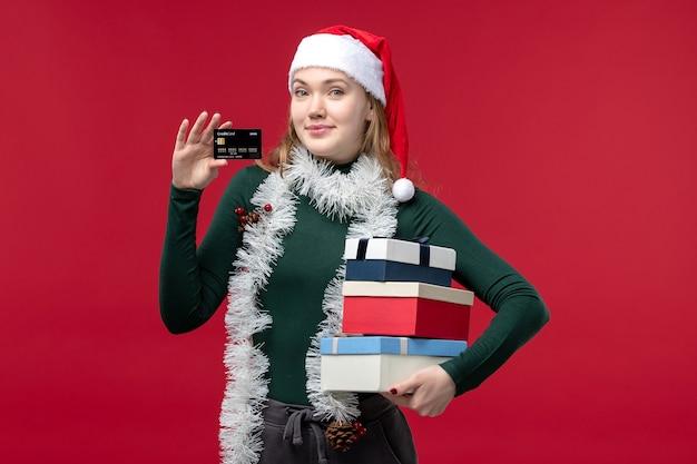 赤い背景に新年のプレゼントを保持している正面図若い女性