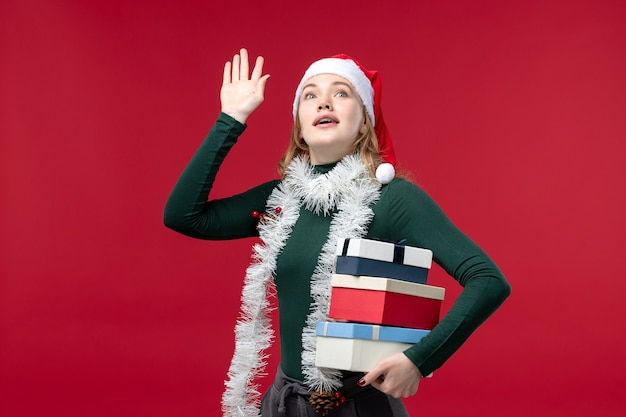 Giovane donna di vista frontale che tiene i regali del nuovo anno su fondo rosso