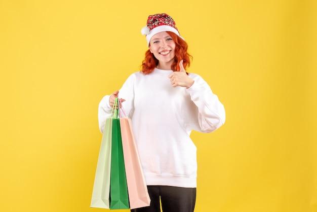 Vista frontale della giovane donna che tiene i pacchetti da acquisti sulla parete gialla