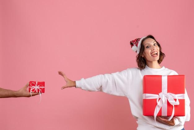 Vista frontale della giovane donna che tiene presente con l'uomo che le sta dando un altro presente sulla parete rosa