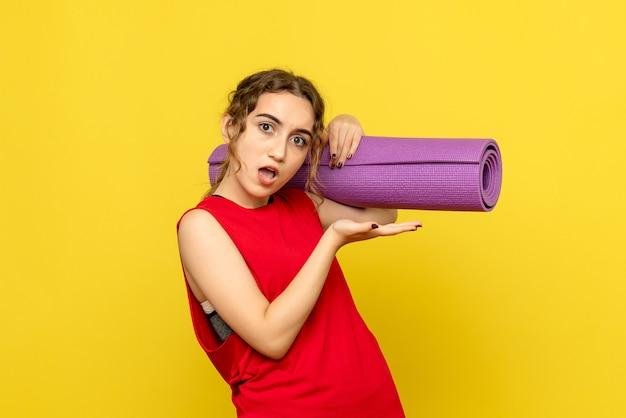 Vista frontale della giovane donna che tiene tappeto viola sulla parete gialla