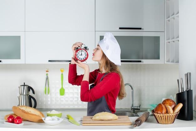 キッチンで赤い目覚まし時計を保持している正面図若い女性