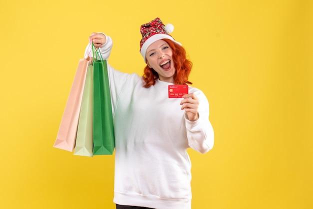Vista frontale della giovane donna che tiene i sacchetti della spesa e la carta di credito sulla parete gialla