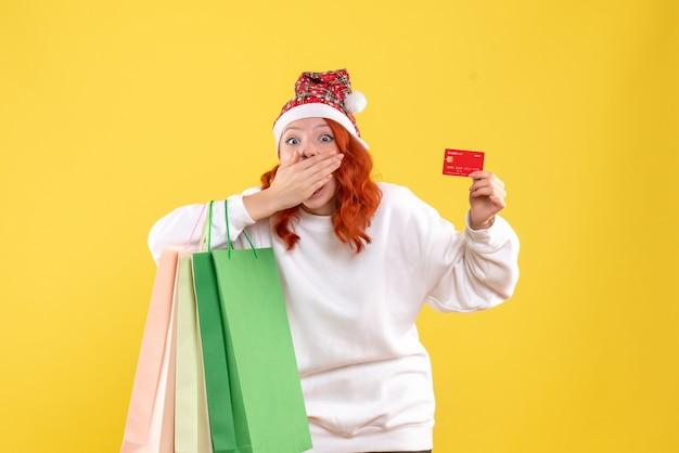 Vista frontale della giovane donna che tiene i pacchetti della spesa e la carta di credito sulla parete gialla