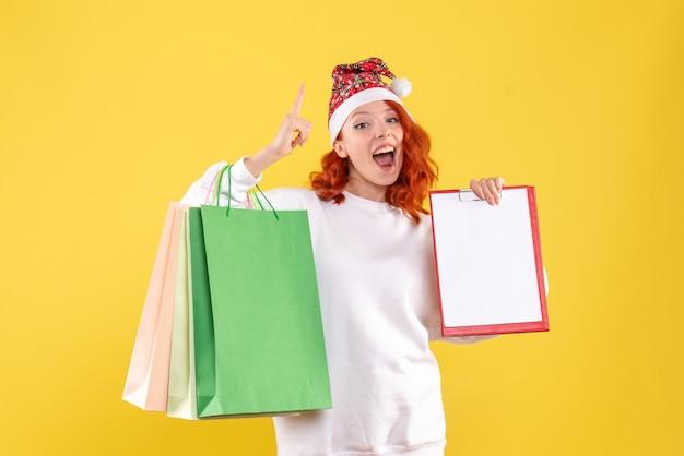 Vista frontale della giovane donna che tiene i pacchetti della spesa sulla parete gialla