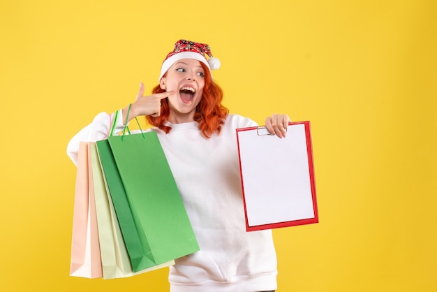 Front view of young woman holding shopping packages on the yellow wall