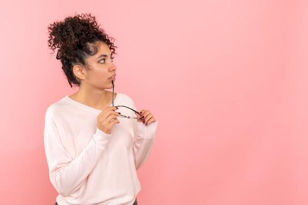 Vista frontale della giovane donna che tiene gli occhiali da sole sulla parete rosa