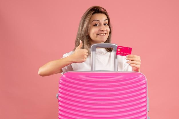 ピンクのスーツケースの後ろに親指をあきらめてチケットを保持している正面の若い女性