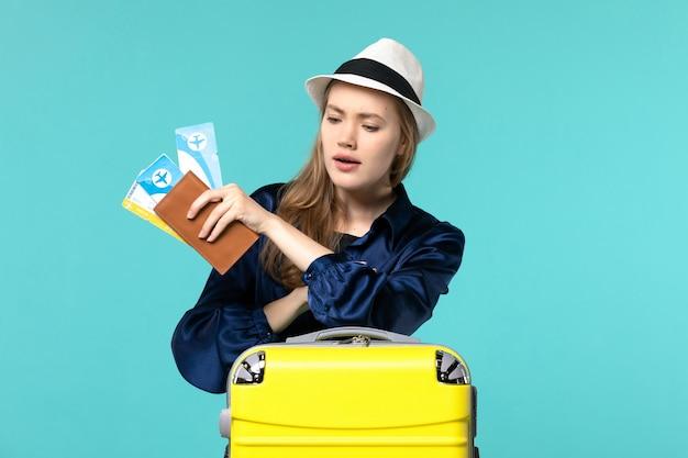 전면보기 젊은 여자 티켓을 들고 파란색 배경 여행 항해 바다 비행기 휴가에 시간을 확인하는 휴가를 준비