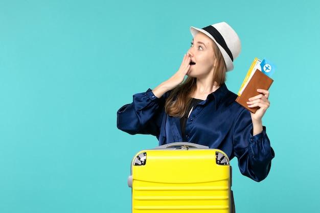 전면보기 젊은 여자 티켓을 들고 파란색 배경 여행 바다 휴가 비행기 항해 여행에 뭔가를 찾고 휴가를 준비