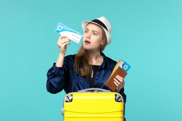 전면보기 젊은 여자 티켓을 들고 파란색 배경 여행 항해 바다 비행기 휴가에 휴가를 준비