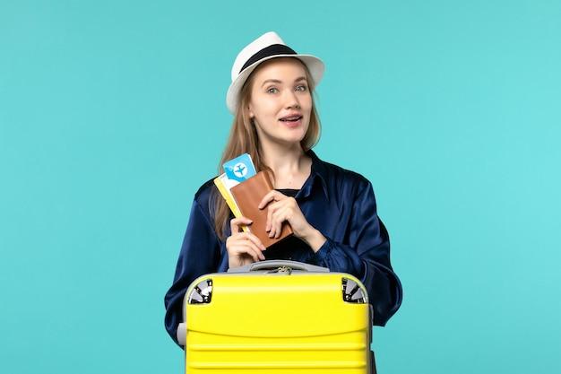 전면보기 젊은 여자 티켓을 들고 파란색 배경 비행기 여행 바다 휴가 항해 여행에 휴가를 준비