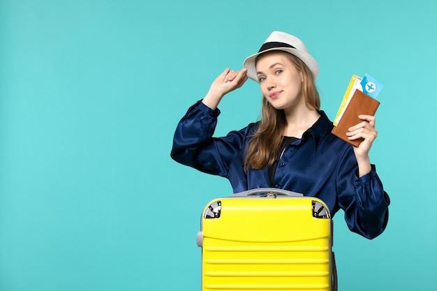 전면보기 젊은 여자 티켓을 들고 파란색 배경 여행 바다 휴가 비행기 항해 여행에 휴가를 준비