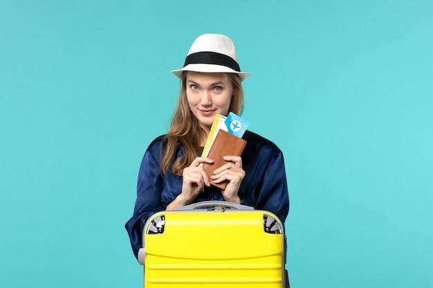 전면보기 젊은 여자 티켓을 들고 파란색 배경 여행 바다 휴가 여행 비행기 항해에 휴가를 준비