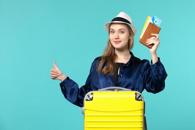 전면보기 젊은 여자 티켓을 들고 파란색 배경 여행 바다 휴가 여행 비행기 항해에 미소 휴가를 준비