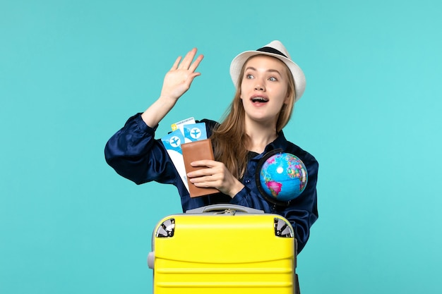 Front view young woman holding tickets and globe on a blue background plane sea vacation journey voyage