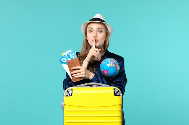 Front view young woman holding tickets and globe on blue background plane sea vacation journey voyage