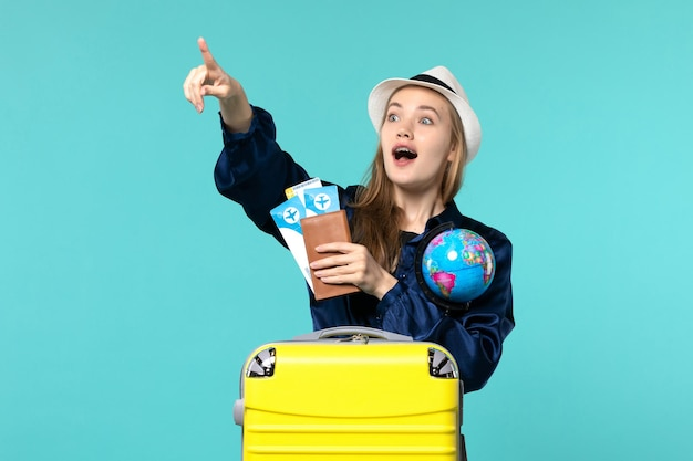 Front view young woman holding tickets and globe on the blue background plane sea vacation journey voyage